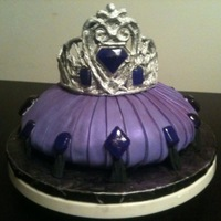 Tiara On Purple Pillow Cake   Tiara is made out of white chocolate, and gems are poured sugar. Cake is a carved red velvet covered with fondant. Tassels are gumpaste.