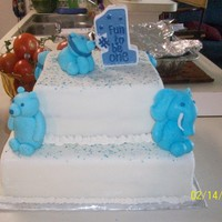 Blue Animal First Birthay Cake   Chocolate cake covered in white fondant and blue sprinkles. Blue toned animals are hand sculpted out of gumpaste.
