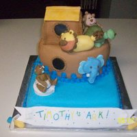 """timothy's Ark"" Baby Shower Cake Cake is covered in fondant with fondant and royal icing accents. Baby, life preserver, animals, banner and pacifiers are gumpaste."
