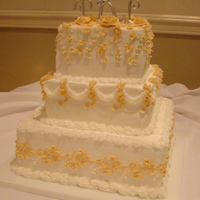 Square Traditional Wedding Cake Three tiered square cake with butter cream icing. Each layer a different sign with a soft peach color butter cream. The angle of the photo...