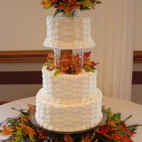 Basket Weave Wedding Cake Butter cream icing with basket weave design accented with fall flowers and pods.