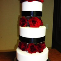 Eelegant Wedding Cake With Red Roses Made with fondant, ribbon, and fresh flowers