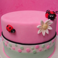 Lady Bugs When i was done with this cake it made me smile :) Its a 6 inch covered with mmf, ladybugs nd daisy are fondant as well. Thanx for looking...