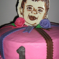 Tiffani's First Birthday Cake This cake was created back in December for my niece's first birthday. Her face is a chocolate portrait. Ribbon roses and ribbon are...