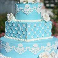Blue And White Wedding Cake (Vow Renewal) Blue buttercream w/ gumpaste designs, gumpaste roses and small blossoms.