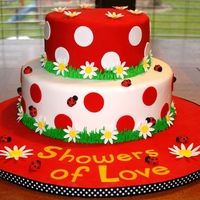 Ladybug Baby Shower Cake Two-tiered fondant cake w/ gumpate daisies and lady bugs.