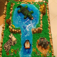 Zoo Cake Cake is covered in buttercream. Animals are made out of fondant. The water is made with piping gel.