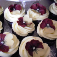 Burgundy Pansies  Burgundy and yellow pansies on dark chocolate cupcakes with yellow vanilla buttercream icing. They went with a cake for a graduation party...