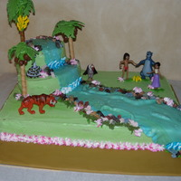 "Jungle Book Cake 1/2 sheet base, various rounds and oval cakes stacked and carved to create ""mountain"" covered cake in green buttercream, marbled..."