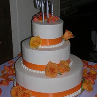 Orange Rose Accents This is a simple round 3 tiered wedding cake decorated with an orange ribbon and orange roses. The top 2 tiers are white cake with...