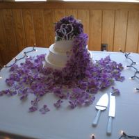 Cascading Purple Flowers A lemon cake with raspberry filling, this 3 tiered cake is frosted with buttercream and decorated with faux purple flowers. I created the...