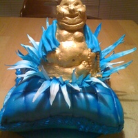 Buddah On Lotus Flower Pillow cake covered with fondant. RKT hand molded budah covered with melted chocolate then airbrushed. Gumpaste lotus flower