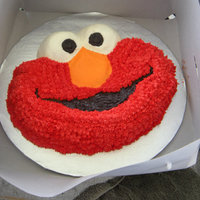 Elmo Cookie Cake This is a chocolate chip cookie cake. A cookie cake is a really really big cookie!! :D Yumm! Its decorated with buttercream icing.