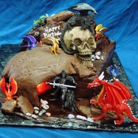 Dungeons And Dragons Birthday cake for gamer. This cake has a lit fire burning inside a sculpted fudge cavern in front of cake mountain covered in dragons with...