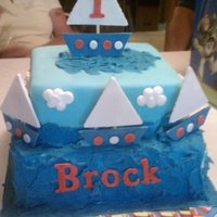 Sailboat Birthday Cake First birthday cake with a sailboat theme. Boats are made of gumpaste, fondant covering the tiers, water is buttercream.