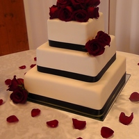 Classic Red Rose Wedding Cake 6 9 and 12 inch square wedding cake. Middle tier is Dark Chocolate Cake with Raspberry Filling and Chocolate Fudge BC. The other 2 tiers...