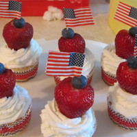 Freedom Cakes Blueberry cupcakes with buttercream icing topped with a strawberry, blueberry and American Flag