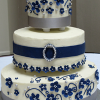White, Navy, And Silver Wedding Cake This is my first wedding cake--three tiers with two different types of cake, white chocolate cream cheese buttercream. Flowers and the &...