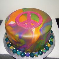 Peace Edible glitter peace sign made free-hand from fondant. I marbled the fondant to look like tie-dye.