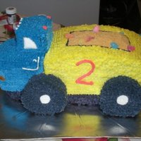Dump Truck Cake   Sculpted cake with buttercream icing, some royal icing windows, graham cracker crumbs as the dirt, with candy worms and gumdrops.