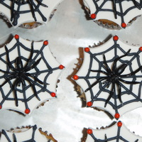 Spiderweb Cupcakes Cupcakes topped with a fondant cutout spiderweb and a plastic spider.