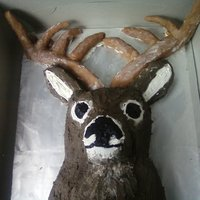 Deer Head   Cake is made out of a sheet cake carved into the shape of a deer. The antlers are formed out of fondant.