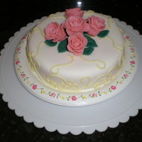 Two Layer Lemon Cake Two layer lemon cake with organic strawberry filling and lemon butter cream icing. Cake is covered in fondant with fontand roses and leaves...