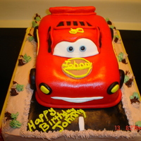 Lightning Mcqueen Cake Hand carved from vanilla cake and covered in fondant sitting on top of half sheet cake covered in buttercream.