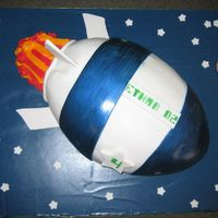 Rocketship Cake Child's birthday cake. Fondant with blue luster dust painted on two blue fondant sections. Fondant stars and planet on a board covered...