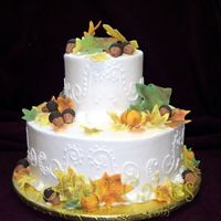 Two Tier Fall Theme Wedding Cake  This was a small wedding cake with fondant leaves, pumpkins and acorns. I just love the fall colors. I hope I get to do a larger version of...