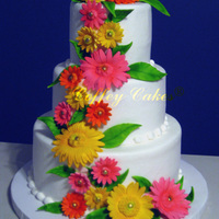Gumpaste Daisy Cascade.   The bride wanted bright neon colored Daisys with neon green leaves so I think these fit the bill.The cake is iced in buttercream.