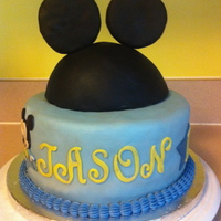 Mickey Mouse 1St Birthday Cake covered in fondant with fondant accents. Ears are made of rice cereal treats covered in fondant.