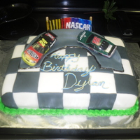 Nascar Cake This is a little boys Nascar cake. The cake was vanilla with butter cream filling and was all fondant decor. The cares were toys.