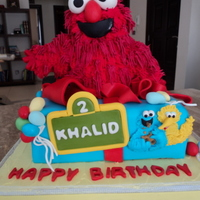 Elmo 10-inch cake with Elmo made from RKT and piped with RI (Wilton grass tip). Cookie Monster, Big Bird, Oscar and accents are made from...