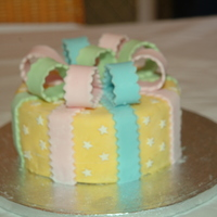 "Yellow Bows  6"" round Madeira cake with yellow fondant, white stars and pastel coloured bows & ribbons. Taken from the Wilton fondant book for..."