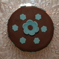 "Blue Flowers   4 "" round Madeira cake with chocolate brown fondant and blue fondant flowers. Just a practice cake I made."