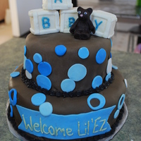 Brown And Blue Baby Shower Cake Two tiered marble cake covered in brown fondant with blue and white circle accents. Teddy bear and blocks made of fondant.