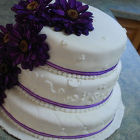 Wedding Cake All vanilla 3 tiered wedding cake with purple daisies.