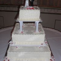 Three Tier Wedding Cake   Covered in butter cream and accented with fondant flowers.