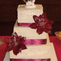 Christmas Wedding   Buttercream cake with gumpaste poinsettias, satin ribbon, and silver dragees.