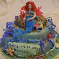 Mermaid Cake  This was for an 11 year old young lady who likes mermaids. Cake is chocolate covered with fondant. Accents are made of hard candy, fondant...
