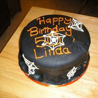50Th Birthday On Halloween 10 inch round white cake with vanilla buttercream covered in black fondant. Webs are white chocolate and spiders are fondant. Made this...