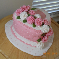 "8"" Heart W/carnations 8"" heart with pink fondant, pink and white carnations and pink roses. Board and side of cake have diamond pattern with tiny white and..."