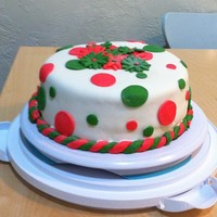 Polka Dot Cake Cake covered in white MMF. Decorations also made of pink and green MMF.