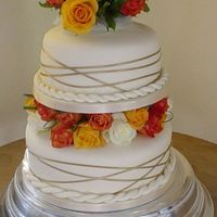 Autumn Wedding Cake Two tiers decorated with fresh roses in Autumn colours, and gold ribbon spun around the edge