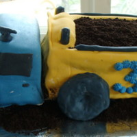 Dumptruck Birthday Cake   fondant covered, dirt in back food proccesed oreos, wheels are hostess donuts covered with fondant