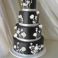 Black And White Wedding Cake Black fondant with royal icing piping and gumpaste flowers.