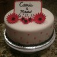 "First Daisy Cake 10"" white cake with buttercream covered in fondant. Buttercream border and swiss dots. Gumpaste daisies and plaque (held up by lolly-..."