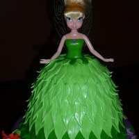 Tink!  Tinkerbell doll w/ carved cake skirt - Vanilla Cake w/ Peanut Butter Buttercream covered in MMF leaves. Base cake is Chocolate Cake w/...