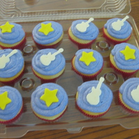 Hannah Montana Theme Vanilla Cupcakes with cream cheese frosting. Toppers are fondant stars and white chocolate guitars. TFL